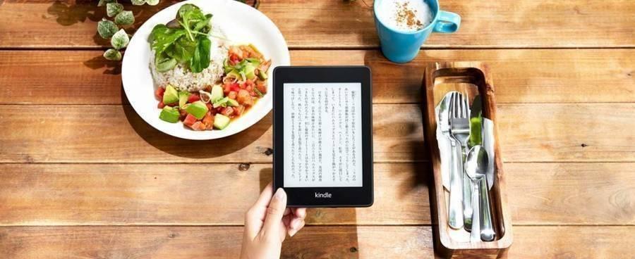 明るい食卓の上で「Kindle Paperwhite」を持っている画像